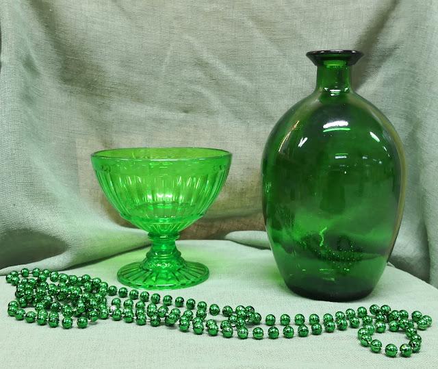 Vihreä kangastausta ja pohja, vihreä muovikulho, vihreä helmikoru, ja vihreä maljakko.