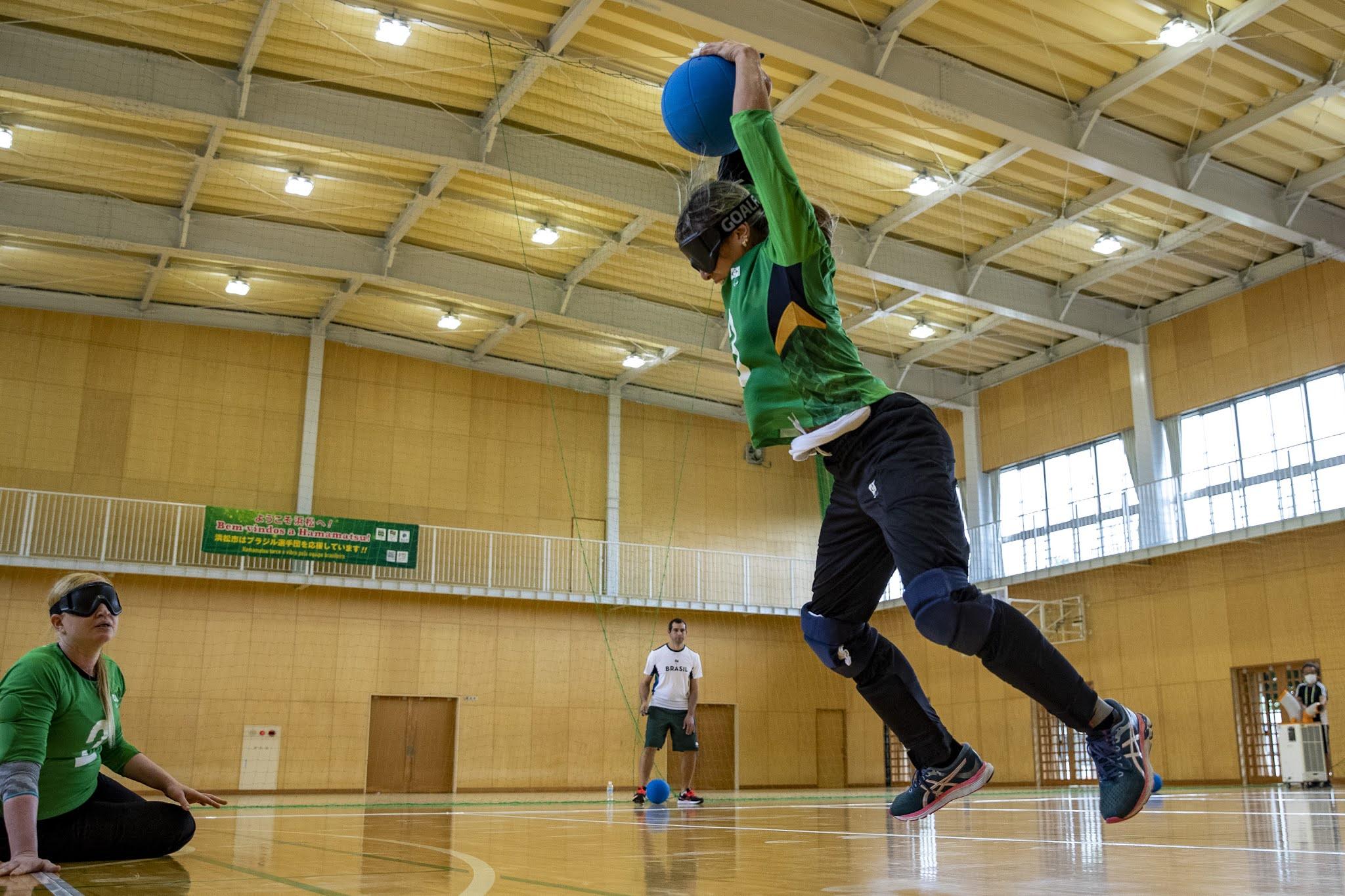 Jogadora brasileira com a bola acima da cabeça se preparando para um arremesso durante treinamento
