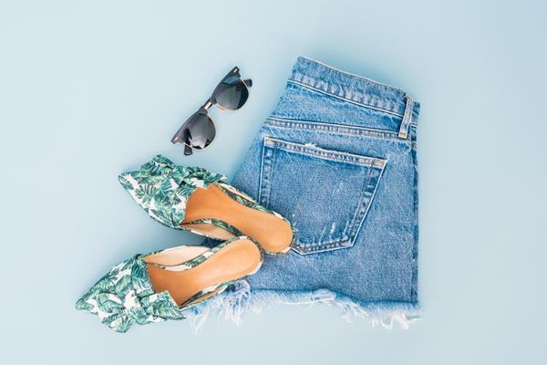 flatlay-shorts-dobrado-mule-e-oculos-de-sol-em-um-fundo-azul