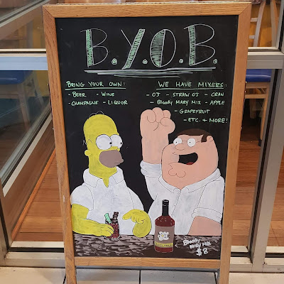 'Homer Simpson' and 'Peter Griffin' on a chalkboard sign in Chicago