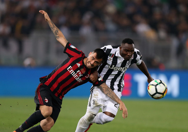 Kwadwo Asamoah of Juventus competes for the ball with Fernandez Suso of AC Milan during the TIM Cup Final between Juventus and AC Milan at Stadio Olimpico on May 9, 2018 in Rome, Italy