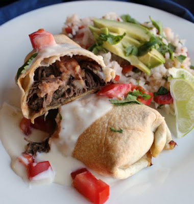 inside of a baked barbacoa chimichanga topped with queso and tomatoes