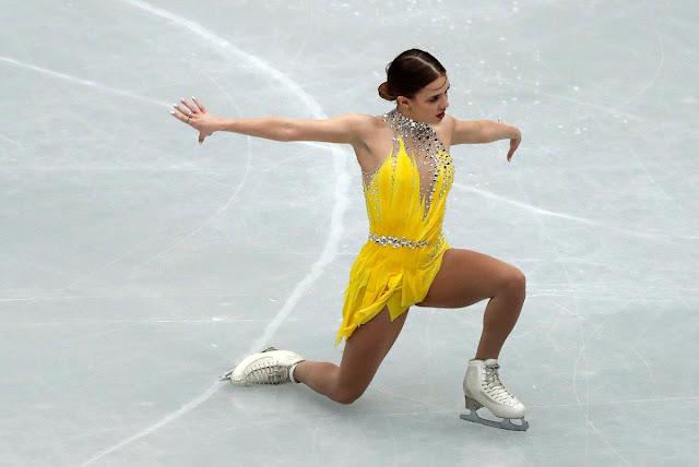 Isadora Williams durante apresentação. Ela usa um vestido amarelo, cabelo preso com um coque e está ajoelhada no gelo