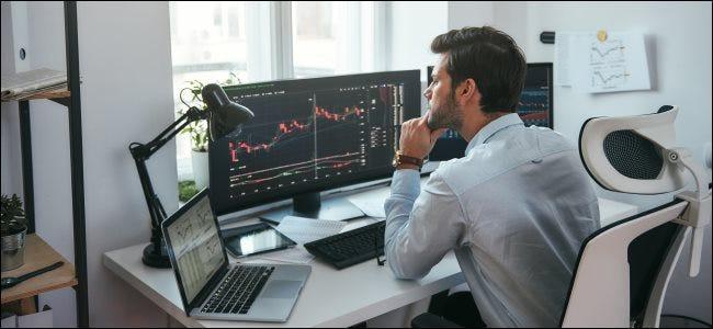 رجل في مكتب ينظر إلى جهاز MacBook وشاشتين كبيرتين لسطح المكتب.