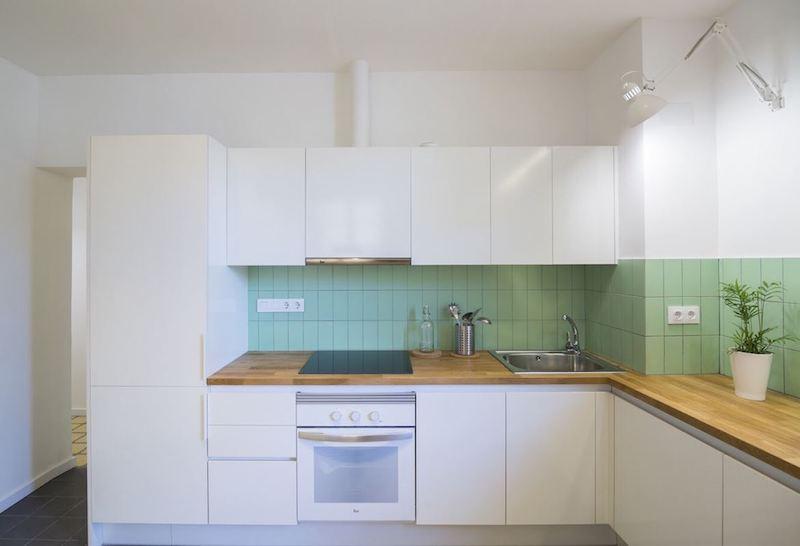 Cocina abierta al salón con frente color verde