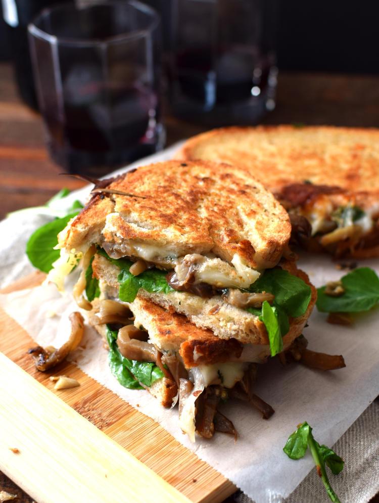 Sándwich de berenjena cortada a la mitad, servido sobre una tabla de madera