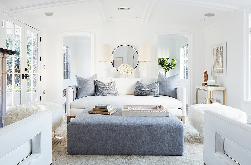 """Midcentury modern style in a modern farmhouse living room with white decor. """"I wanted every wall to make sense, to have its own vignette,"""" says Alex. It's also a flexible design scheme—the ottoman adds extra seating and can be """"scooched up for cozier conversations during parties."""""""