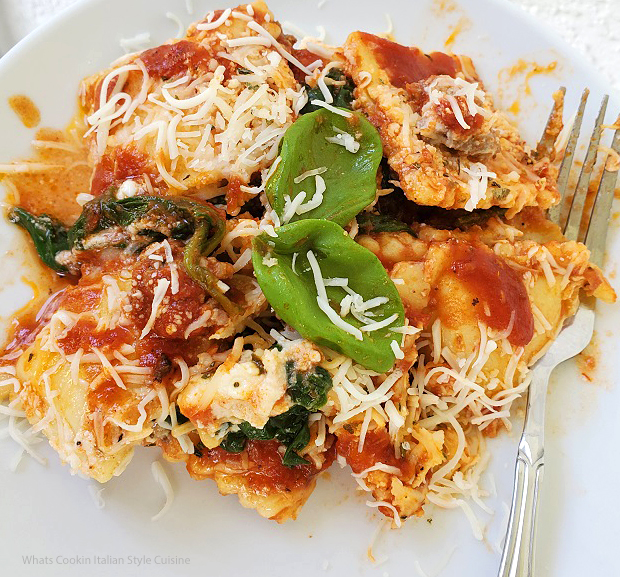 this is bake ravioli on a plate with basil on a white plate sprinkled with shredded cheeses