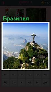 на высоком холме стоит памятник и видна панорама Бразилии