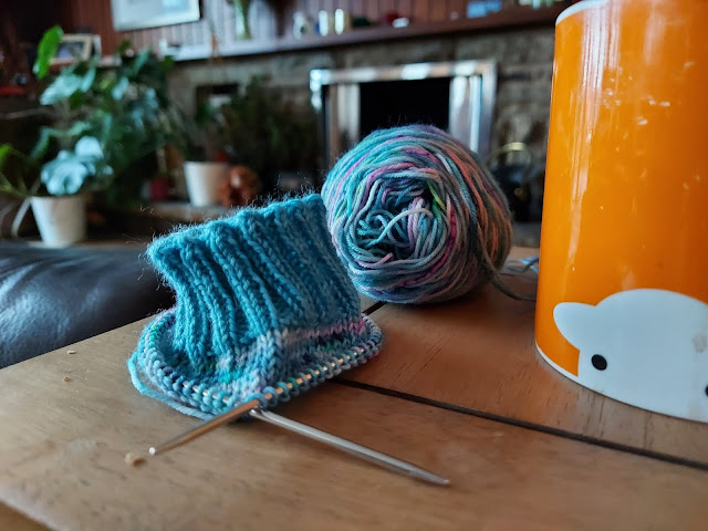 A partly knitted sock on a circular needle in shades of turquoise and pink.  There is an orange mug next to it and in the background, houseplants and a fireplace