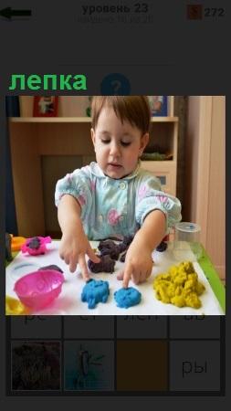 За столом сидит ребенок и занимается лепкой из пластилина