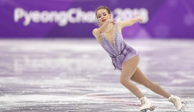 Isadora patina usando um vestido lilás. No fundo, a logo da Olimpíada de Inverno de 2018