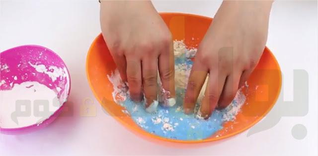 قم بوضع الماء المُلون في الوعاء مع نشا الذرة. صُب الماء المُلوّن ببطء، واستخدم أصابعك لخلط المكونات معًا، اخلط المكونات جيدًا حتى يتحول قوامها إلى معجون سميك.