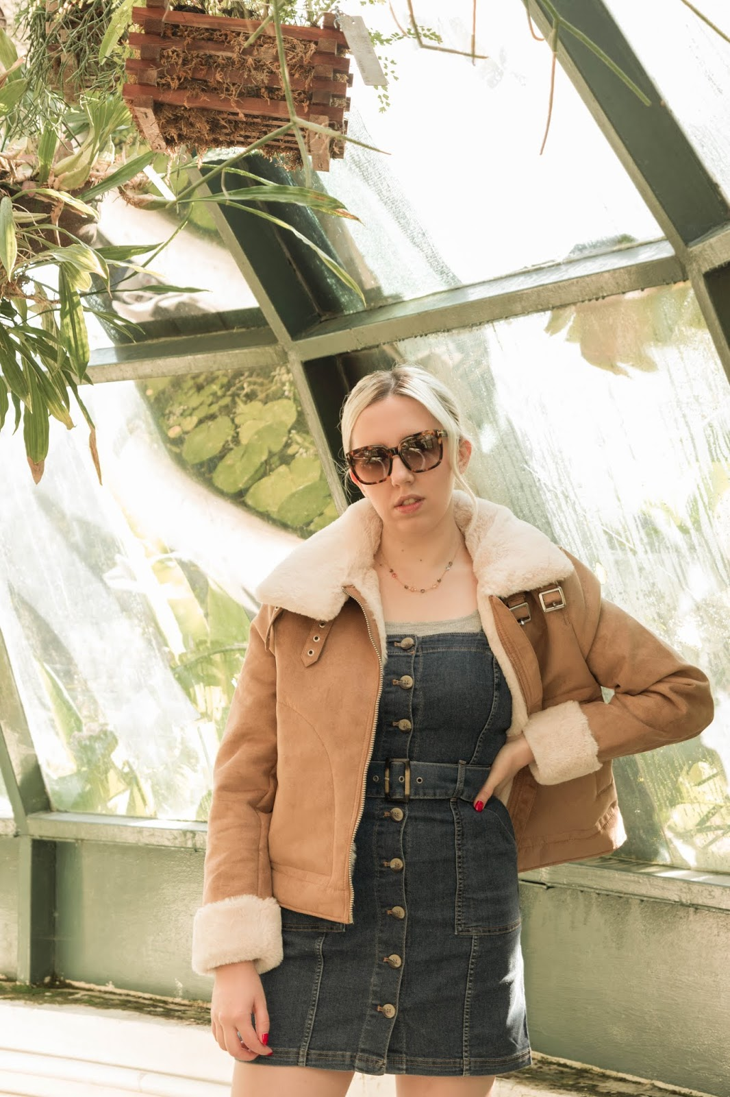 Blonde fashion blogger wearing a pinafore denim dress and aviator jacket for Autumn in Botanical garden