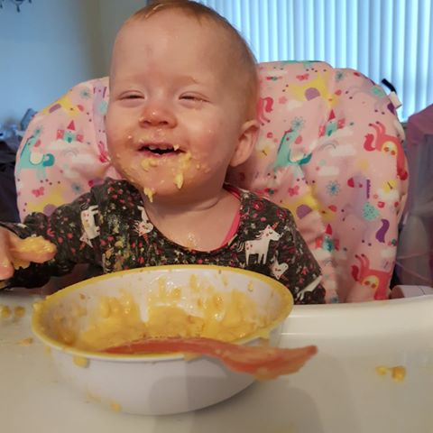 A baby covered in food with a bowl and spoon in front of her