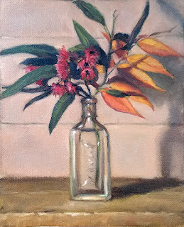 Still life oil painting of flowering gum flowers and leaves, and orange autumn leaves, in a small glass bottle.