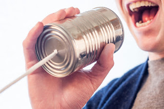 A person is talking into a tin-can with a string at the bottom of it.
