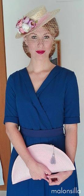 Invitada a boda con vestido azul azafata y sombrero paja con velo y flores & bolso abanico en rosa y malva