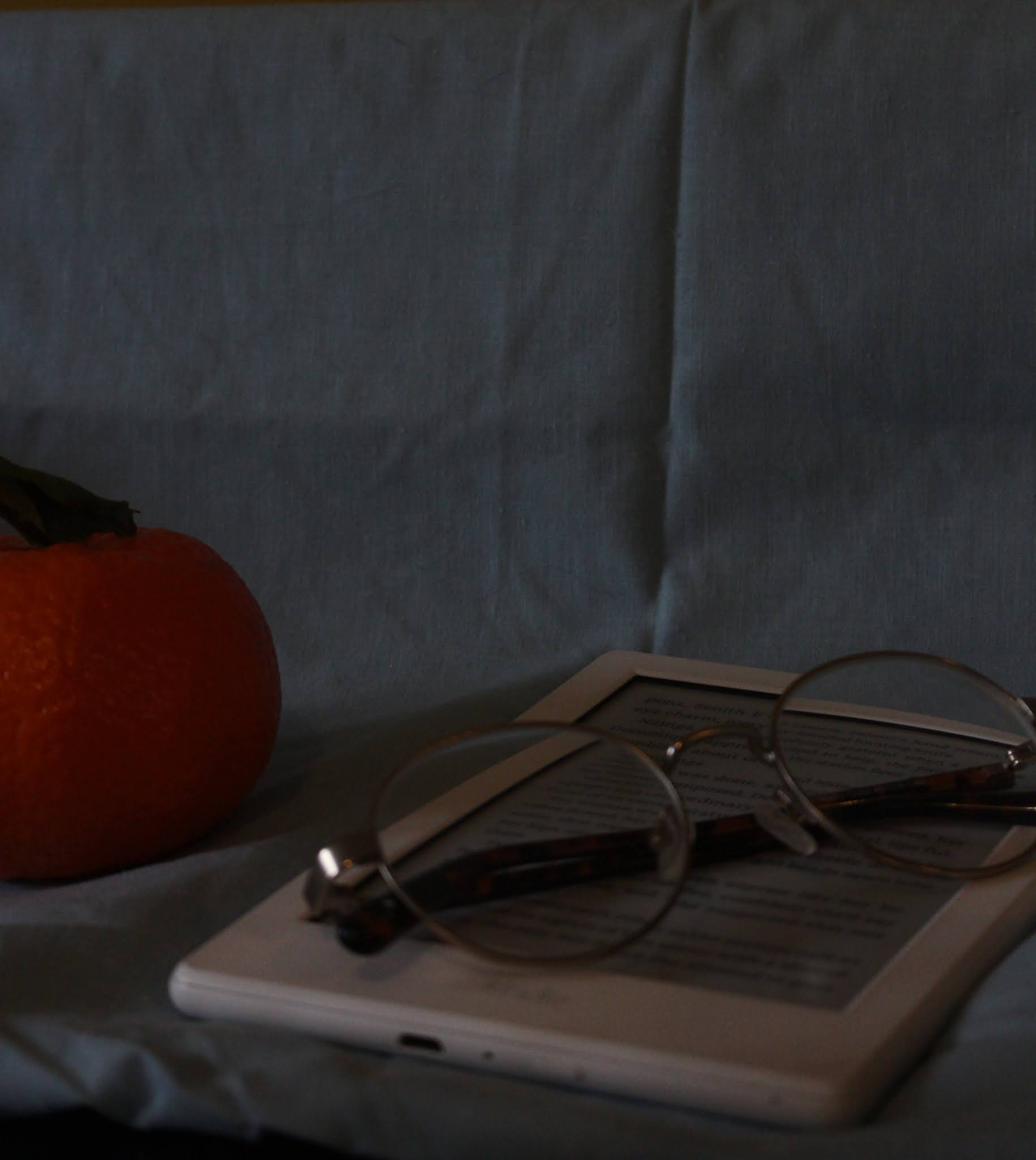 A clementine, white kindle and glasses