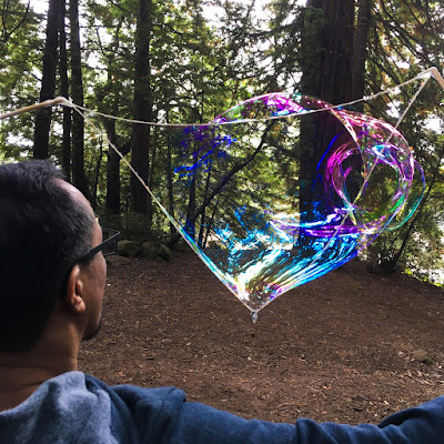 Close up of a man producing a large, elongated soap bubble using sticks and string