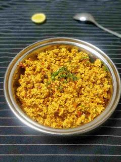Serving paneer bhurji,  lemon wedges and spoon in background