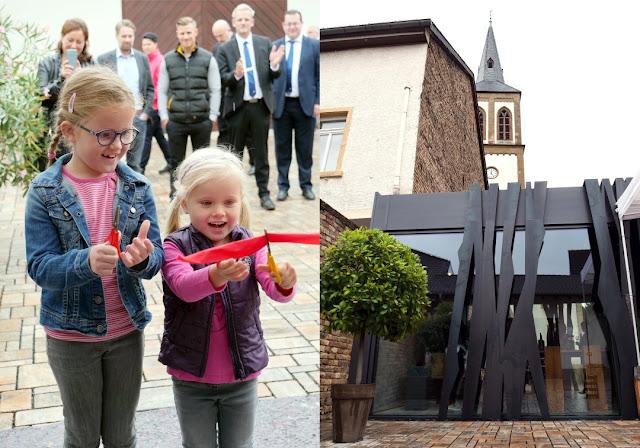 uise und Laura Closheim zerschneiden zur Eröffnung das rote Absperrband vor der Türe der Vinothek Closheim.