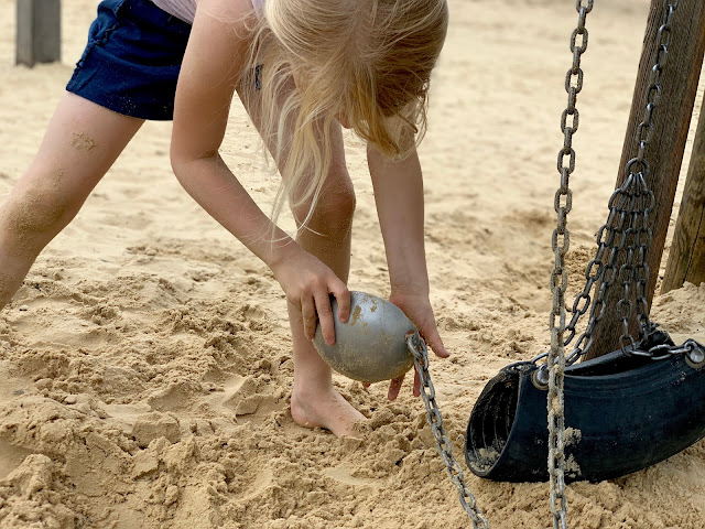 Girl playing with a metal scoop in a sandpit at Great Notley Country Park