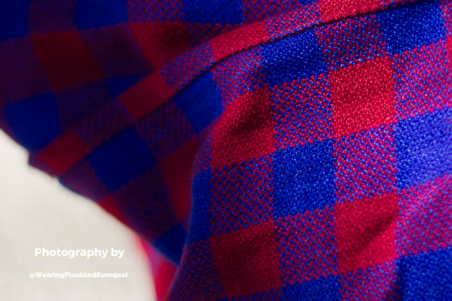 [Close-up image of a red and blue checkered fabric. Artisan hands wove the fibers together in the visible twill weave to support and snuggle your sweeties. See the snuggles. Breathe the snuggles.]