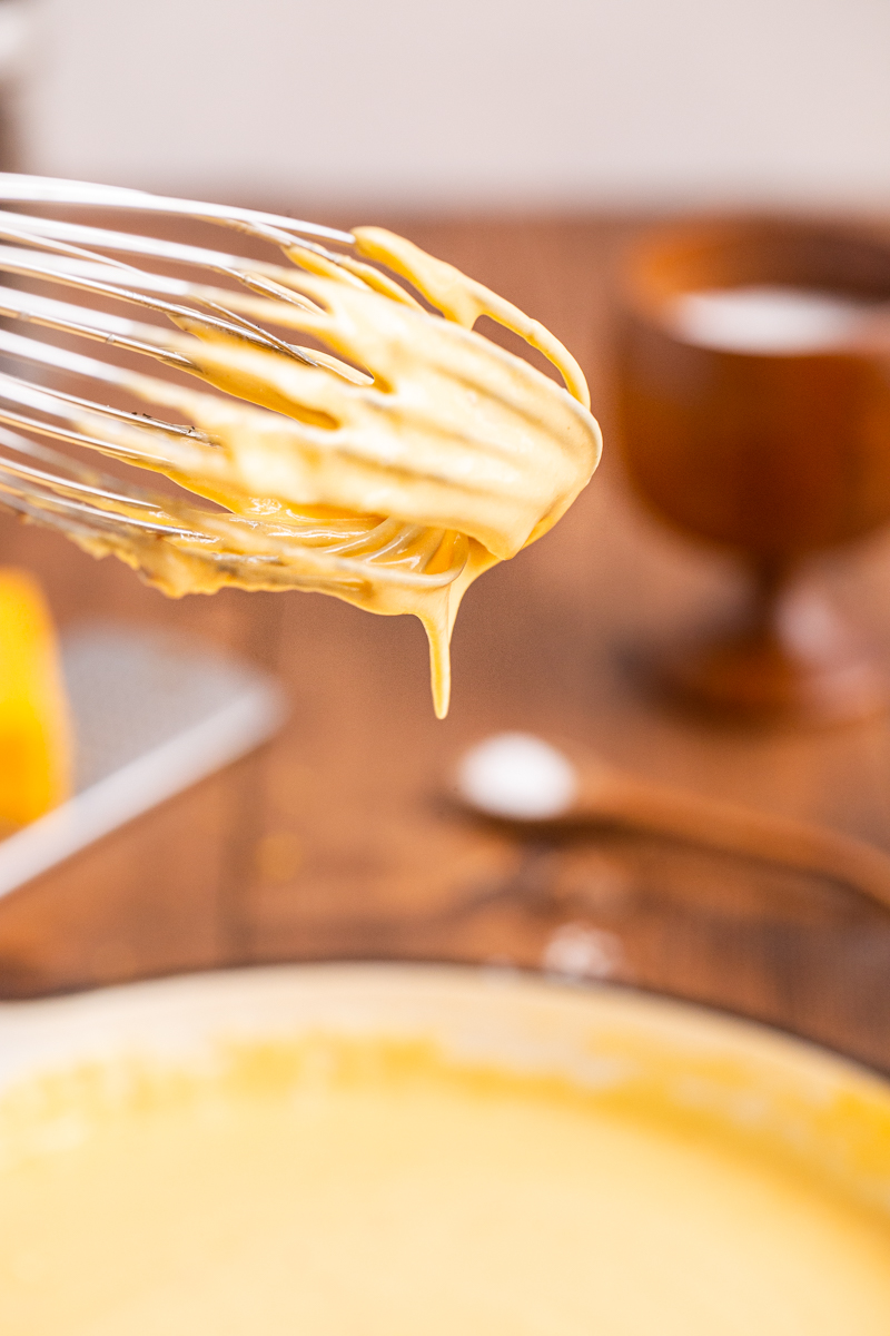 Close up photo of a whisk coated with Easy Keto Cheese Sauce above a skillet.