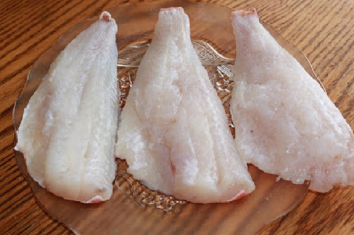 this is three pieces of raw fish getting ready to be breaded and fried on a clear glass plate