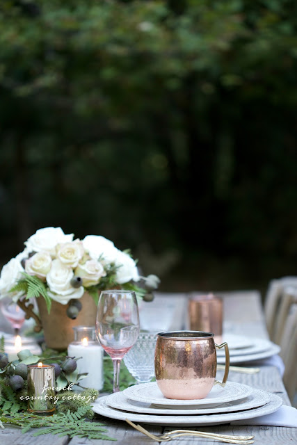 outdoor table set with copper and fresh greens and flowers