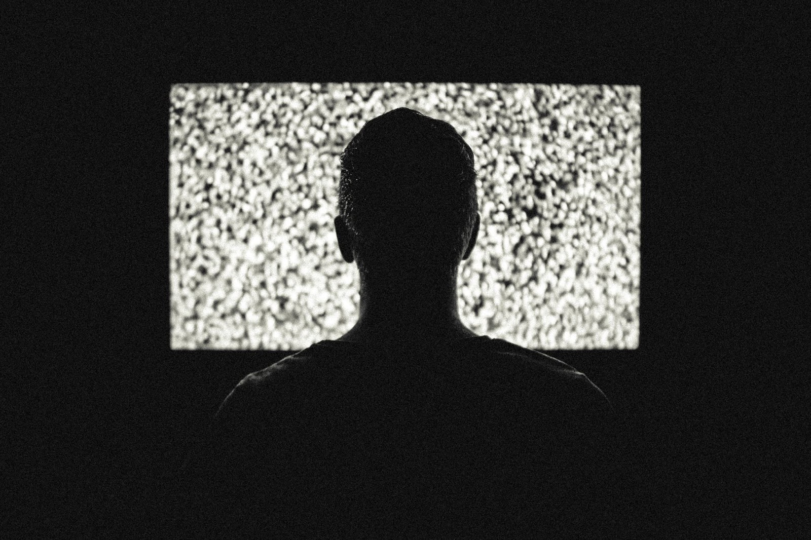 man in front of a television with no signal