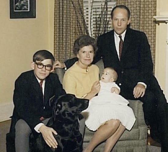 Professional-style family portrait from left, teenaged boy with glasses, labrador retriever dog, woman seated with baby on her lap, man seated on the arm of her chair