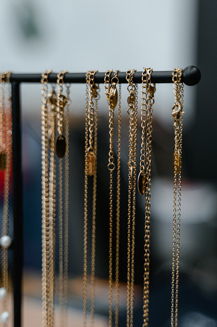 Delicate gold chain necklaces on a T-bar jewelry display stand.