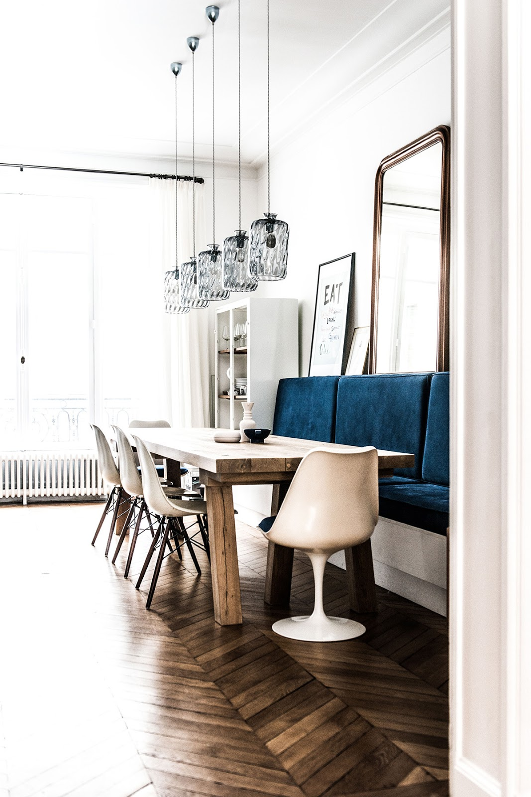 bohemian and chic paris apartment with parquet floors, eames and saarinen chairs, tom dixon lamps and wallpapers, dining room