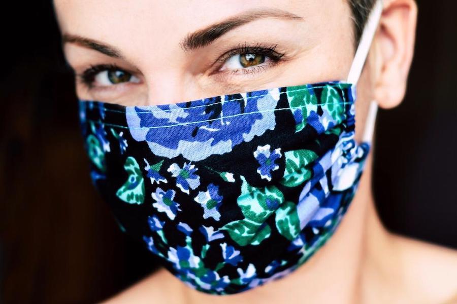 Eine Frau trägt eine bunte Stoffmaske als Mund- Nasenschutz