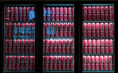 Unsplash - Ashkan Forouzani: Cans of soda displayed in refrigerated cases