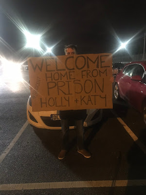 a man stood in front of a car holding a giant cardboard sign that says welcome home from prison holly and katy
