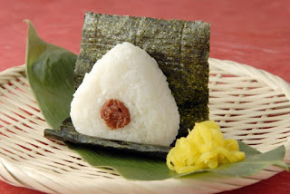 White rice molded into the shape of a triangle, a red dot of pickled plum at its center, wrapped with black nori seaweed.