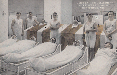 men wrapped in towels lying down in a spa with attendants behind them
