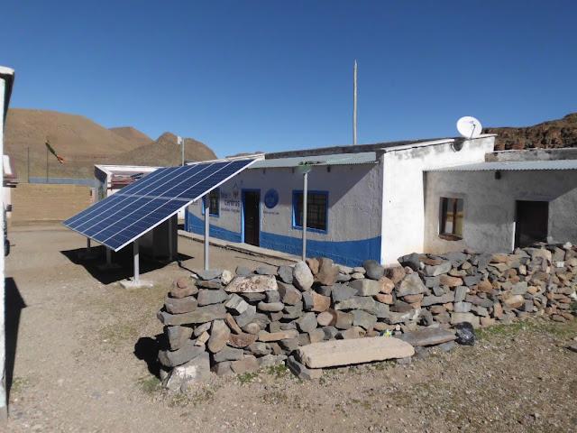 Die vielen Sonnenpannels vor einem weiß blau gestrichenen Raum ist das Telecentro, wo unser Internet, Fernsehen und Telefon untergebracht ist.