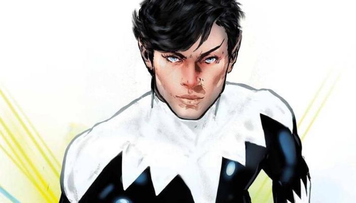 Homem branco de olhos muito claros, quase brancos. Seus cabelos são pretos e lisos, com uma franja ondulada na testa. Ele está sério e olha para frente. Seu uniforme é preto e branco, com formatos triangulares.