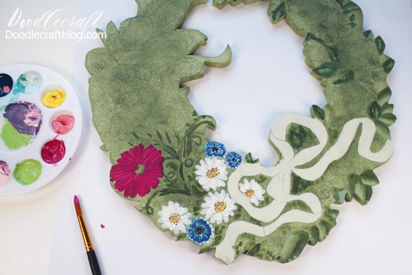 Painting a gerber daisy on a wooden cut out wreath.