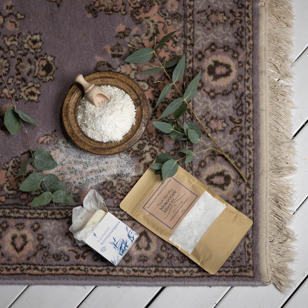 Kuvassa vanhan itämaistyylisen plyysimaton päällä erilaisia ekologisia kodinsiivoustarvikkeita.