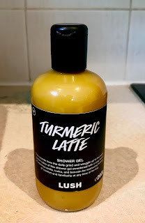 A long cylindrical bottle filled with dark golden liquid with a black cylindrical lid and black rectangular label with turmeric latte in bold white font with Lush in white smaller chunky font at the bottom on a bright background