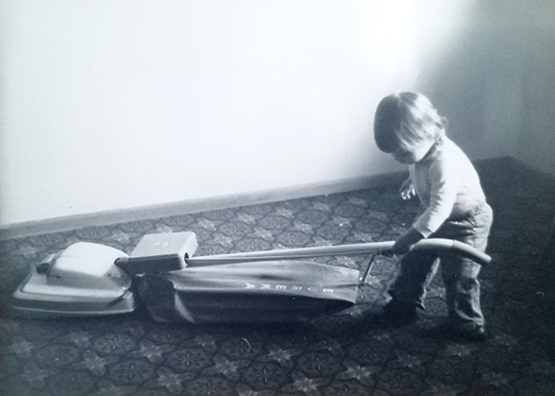 black and white image of me as a baby, trying to use a vacuum