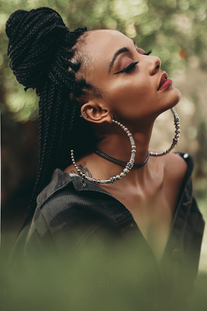 African woman wearing large hoops earrings.