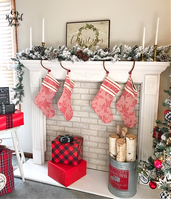red toile Christmas stocking fireplace wrapped Christmas gifts birch logs