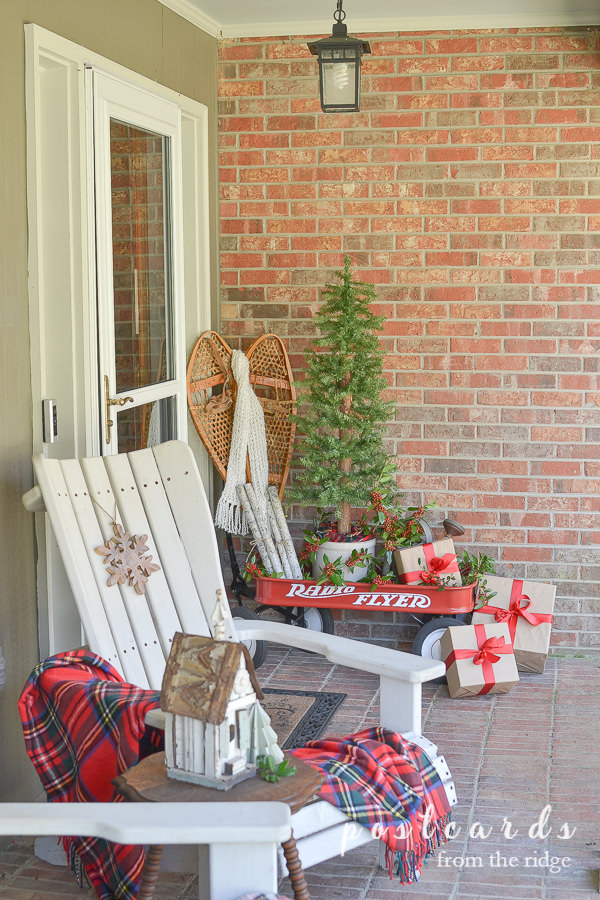 white chair and red wagon with Christmas decor on front porch.