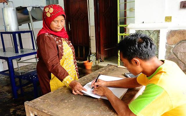 Petugas lain mencatat jumlah setoran susu perahan dari Bu Siamah
